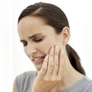Young Woman Holding the Side of Her Face in Pain